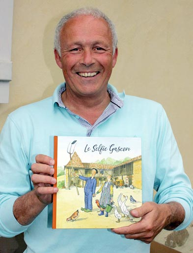 Perry Taylor with his third book of humorous drawings, Le Selfie Gascon
